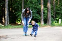 Ευτυχής μητέρα που περπατά με το γιο της στο πάρκο στοκ εικόνες με δικαίωμα ελεύθερης χρήσης