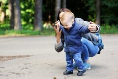 Ευτυχής μητέρα που περπατά με το γιο της στο πάρκο στοκ φωτογραφίες