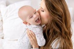 Ευτυχής μητέρα που φιλά το λατρευτό γιο μωρών της οικογένεια ευτυχής Μητέρα και νεογέννητο παιχνίδι παιδιών Στοκ Εικόνες