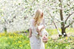 Ευτυχής μητέρα που χορεύει με την κόρη μωρών στην ανθίζοντας Apple Orcha Στοκ Φωτογραφίες