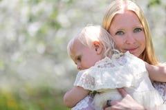 Ευτυχής μητέρα που χορεύει με την κόρη μωρών στην ανθίζοντας Apple Orcha Στοκ Εικόνες