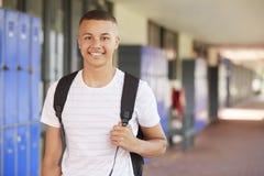 Ευτυχής μικτός έφηβος φυλών που χαμογελά στο διάδρομο γυμνασίου στοκ εικόνες
