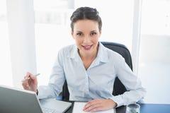 Ευτυχής μοντέρνη επιχειρηματίας brunette που παίρνει τις σημειώσεις και που εξετάζει τη κάμερα Στοκ φωτογραφία με δικαίωμα ελεύθερης χρήσης