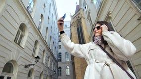 Ευτυχής μοντέρνος θηλυκός τουρίστας που παίρνει selfie κοντά στο ευρωπαϊ φιλμ μικρού μήκους