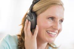 Ευτυχής μουσική ακούσματος γυναικών μέσω των ακουστικών Στοκ φωτογραφίες με δικαίωμα ελεύθερης χρήσης