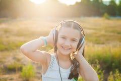 Ευτυχής μουσική ακούσματος κοριτσιών με τα ακουστικά Στοκ φωτογραφία με δικαίωμα ελεύθερης χρήσης