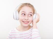 Ευτυχής μουσική ακούσματος κοριτσιών παιδιών χαμόγελου στα άσπρα ακουστικά Στοκ Εικόνες