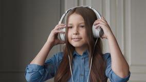 Ευτυχής μουσική ακούσματος παιδιών ή όμορφο χαμογελώντας κορίτσι με τ απόθεμα βίντεο