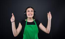 Ευτυχής μουσική ακούσματος πωλητών κοριτσιών από τα ακουστικά της Στοκ Εικόνα