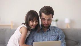 Ευτυχής μπαμπάς και χαριτωμένα κινούμενα σχέδια προσοχής κορών παιδιών στο lap-top απόθεμα βίντεο
