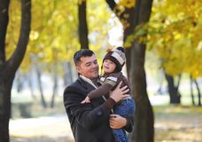 Ευτυχής μπαμπάς που κρατά το γιο του, λίγο αστείο αγόρι παιδιών στο βραχίονα, την κρύα ημέρα, που στέκεται μαζί στο πάρκο φθινοπώ Στοκ Εικόνες