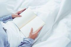 Ευτυχής νέα ασιατική απόλαυση γυναικών τρόπου ζωής που βρίσκεται στην ευχαρίστηση βιβλίων ανάγνωσης κρεβατιών στον περιστασιακό ι στοκ εικόνα
