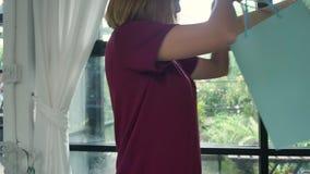 Ευτυχής νέα ασιατική γυναίκα με τις τσάντες αγορών στο σύγχρονο διαμέρισμα που ελέγχει τις αγοραες φιλμ μικρού μήκους