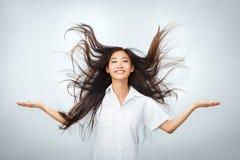 Ευτυχής νέα ασιατική γυναίκα με το όμορφο πέταγμα μακρυμάλλες Στοκ Εικόνες