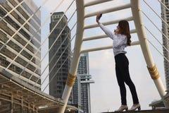 Ευτυχής νέα ασιατική γυναίκα που παίρνει μια φωτογραφία selfie στο αστικό κτήριο με το διαστημικό υπόβαθρο αντιγράφων στοκ εικόνα με δικαίωμα ελεύθερης χρήσης