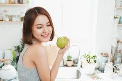 Ευτυχής νέα ασιατική γυναίκα που τρώει την πράσινη Apple στην κουζίνα σιτηρέσιο κύβος Στοκ φωτογραφία με δικαίωμα ελεύθερης χρήσης