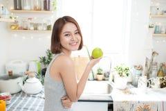 Ευτυχής νέα ασιατική γυναίκα που τρώει την πράσινη Apple στην κουζίνα σιτηρέσιο Στοκ Εικόνα