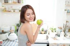 Ευτυχής νέα ασιατική γυναίκα που τρώει την πράσινη Apple στην κουζίνα σιτηρέσιο κύβος Στοκ Εικόνες