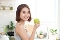 Ευτυχής νέα ασιατική γυναίκα που τρώει την πράσινη Apple στην κουζίνα σιτηρέσιο κύβος Στοκ Εικόνα