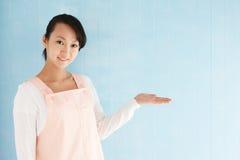 Ευτυχής νέα ασιατική γυναίκα που φορά μια ποδιά Στοκ φωτογραφίες με δικαίωμα ελεύθερης χρήσης