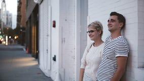 Ευτυχής νέα αυθεντική ρομαντική στάση ζευγών κοντά κατά μια ημερομηνία από τον άσπρο τοίχο οικοδόμησης το βράδυ Soho, Νέα Υόρκη απόθεμα βίντεο