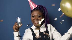 Ευτυχής νέα αφρικανική γυναίκα στο καπέλο γενεθλίων με το γυαλί champanage σε ένα χέρι και το μπαλόνι σε άλλο που χορεύει ενώ απόθεμα βίντεο
