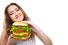 Ευτυχής νέα γυναίκα μεγάλο yummy Burger που απομονώνεται που τρώει Στοκ Φωτογραφία
