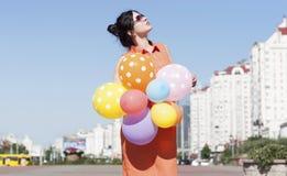Ευτυχής νέα γυναίκα με τα μπαλόνια στο τετράγωνο πόλεων Στοκ Φωτογραφία