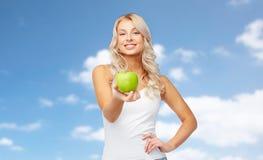 Ευτυχής νέα γυναίκα με το πράσινο μήλο πέρα από το μπλε ουρανό Στοκ Εικόνες