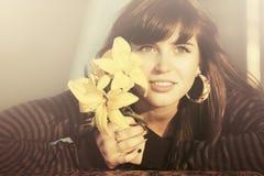 Ευτυχής νέα γυναίκα με το χαμόγελο λουλουδιών υπαίθριο Στοκ φωτογραφία με δικαίωμα ελεύθερης χρήσης