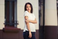 Ευτυχής νέα γυναίκα μόδας στην άσπρη μπλούζα στην οδό πόλεων στοκ εικόνες με δικαίωμα ελεύθερης χρήσης