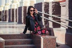 Ευτυχής νέα γυναίκα μόδας στο σακάκι και τα γυαλιά ηλίου δέρματος στοκ εικόνα