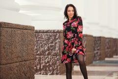 Ευτυχής νέα γυναίκα μόδας στο floral φόρεμα στην οδό πόλεων στοκ εικόνα με δικαίωμα ελεύθερης χρήσης