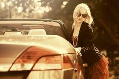 Ευτυχής νέα γυναίκα μόδας δίπλα στο αυτοκίνητό της Στοκ Φωτογραφίες