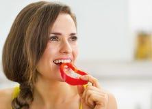 Ευτυχής νέα γυναίκα που έχει ένα δάγκωμα του κόκκινου πιπεριού κουδουνιών Στοκ Εικόνες