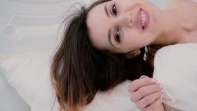 Ευτυχής νέα γυναίκα που έχει τη διασκέδαση στο κρεβάτι Ελκυστικές δορές κοριτσιών κάτω από το κάλυμμα, που παίζει με την τρίχα κα απόθεμα βίντεο