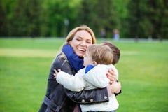 Ευτυχής νέα γυναίκα που αγκαλιάζει τους δύο γιους και το γέλιο Στοκ Φωτογραφία