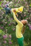 Ευτυχής νέα γυναίκα που ανυψώνει το γιο της υψηλό επάνω Στοκ Εικόνες