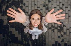Ευτυχής νέα γυναίκα που αυξάνει τα χέρια της επάνω υπαίθρια στοκ φωτογραφία με δικαίωμα ελεύθερης χρήσης