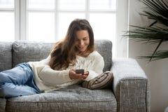 Ευτυχής νέα γυναίκα που βρίσκεται στον καναπέ που χρησιμοποιεί στο σπίτι το smartphone Στοκ Φωτογραφία