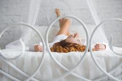 Ευτυχής νέα γυναίκα που βρίσκεται στο κρεβάτι Στοκ Φωτογραφίες