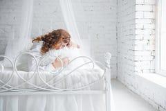 Ευτυχής νέα γυναίκα που βρίσκεται στο κρεβάτι Στοκ Φωτογραφία