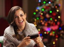 Ευτυχής νέα γυναίκα που γράφει sms κοντά στο χριστουγεννιάτικο δέντρο Στοκ Εικόνες