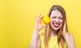 Ευτυχής νέα γυναίκα που κρατά ένα λεμόνι στοκ εικόνες