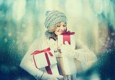 Ευτυχής νέα γυναίκα που κρατά τα παρόντα κιβώτια στοκ φωτογραφίες