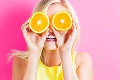 Ευτυχής νέα γυναίκα που κρατά τα πορτοκαλιά μισά Στοκ φωτογραφίες με δικαίωμα ελεύθερης χρήσης