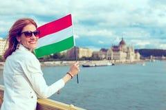 Ευτυχής νέα γυναίκα που κρατά την ουγγρική σημαία στο cinematic ύφος της Βουδαπέστης στοκ φωτογραφία