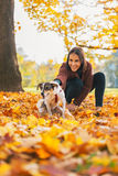 Ευτυχής νέα γυναίκα που κρατά το εύθυμο σκυλί υπαίθρια Στοκ Εικόνες