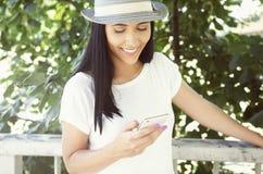 Ευτυχής νέα γυναίκα που κρατά το κινητό τηλέφωνο Στοκ φωτογραφία με δικαίωμα ελεύθερης χρήσης