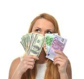 Ευτυχής νέα γυναίκα που κρατά ψηλά τα δολάρια και τα ευρώ χρημάτων μετρητών Στοκ εικόνα με δικαίωμα ελεύθερης χρήσης